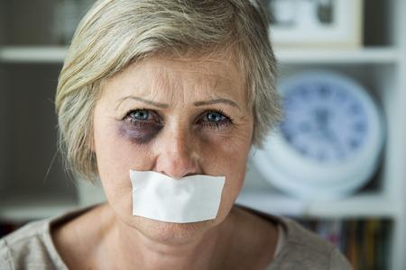 Senior femme avec les yeux noirs et ruban adhésif sur sa bouche, victime de violence conjugale