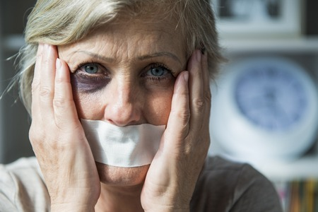 beaten: Senior woman with black eye and tape on her mouth, victim of domestic violence