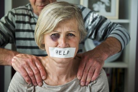 Retrato de la mujer víctima de violencia doméstica hombre abusando de la mujer mayor con el ojo negro y la cinta en su boca Foto de archivo