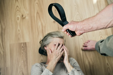 cruelty: Woman victim of domestic violence and abuse  Mature woman with black eye scared of a man with a belt  Stock Photo