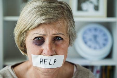 Senior vrouw met een blauw oog en tape op haar mond, slachtoffer van huiselijk geweld