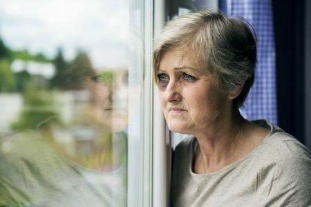 Scared woman is looking through the window  Having bruise on her face Stock Photo