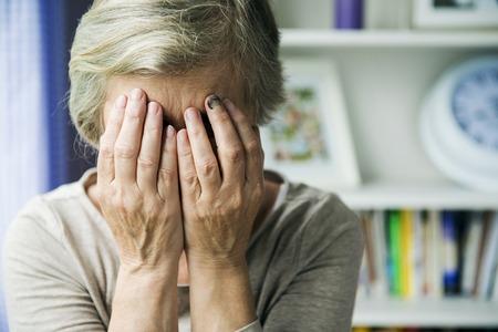 senior depression: Senior woman with black eye is victim of domestic violence Stock Photo