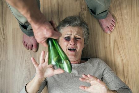 dominacion: Mujer víctima de violencia doméstica y abuso de la mujer madura con el ojo negro miedo de un hombre con una botella rota Foto de archivo