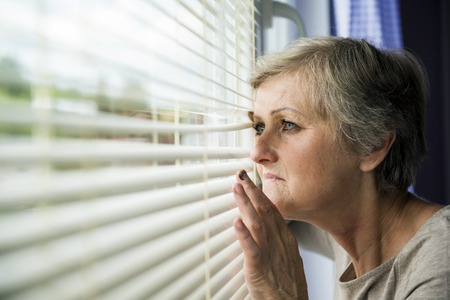 Scared woman is looking through the window Having bruise on her face