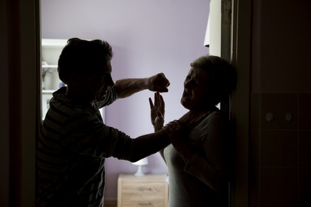 Silhouette of mature couple fighting, the man is physically abusing woman  Woman is victim of domestic violence photo