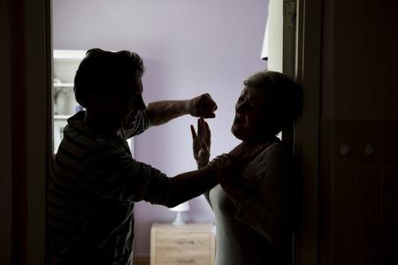 abusing: Silueta de la Lucha contra la pareja madura, el hombre est� abusando f�sicamente mujer La mujer es v�ctima de violencia dom�stica