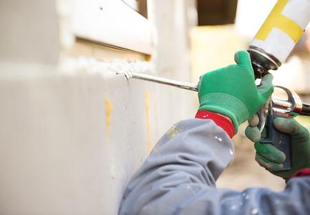 pistola: El hombre de aplicar sellador de espuma con pistola de calafateo para aislar la ventana