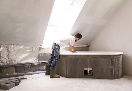 A felújítás fürdőszoba egy építőmunkás