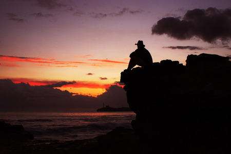 Silhouette of man in hat on the sunset at sea Stock Photo