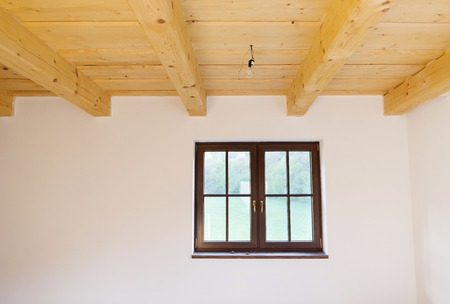 Empty unfinished room with white walls and wooden ceiling in a new constructed house photo
