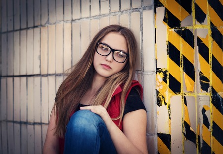 teen girl brown hair: Sad teenage hipster girl sitting by the black and yellow striped warning wall Stock Photo