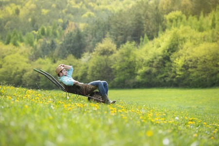 barrow: Young male farmer is relaxing in wheelbarrow on the green meadow