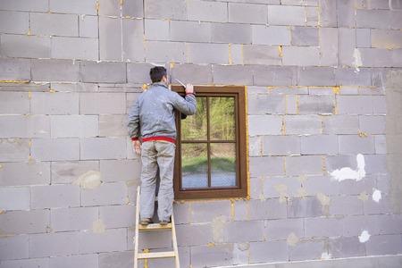 Man applying foam sealant with caulking gun to insulate the window photo