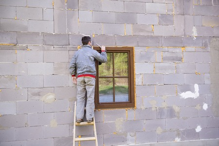 Man applying foam sealant with caulking gun to insulate the window photo