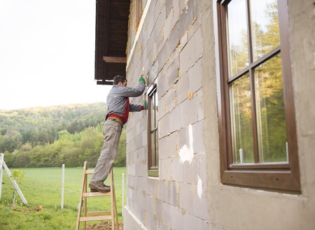 Plasterer spreading out plaster with trowel around the windows Stock Photo