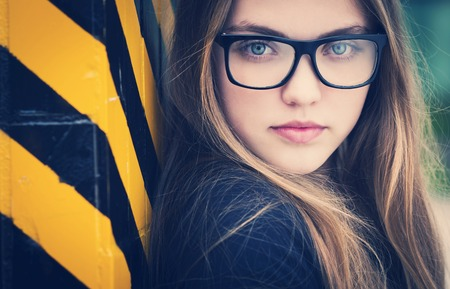 sad person: Portrait of sad teenage hipster girl standing by the black and yellow striped warning wall