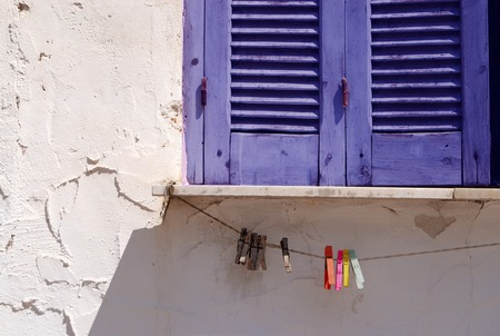 Closed blue window shutters and clothes pins on rope photo