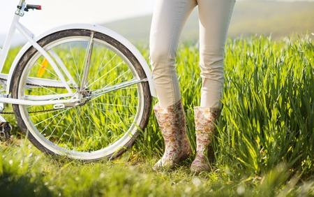 Detail of young woman s feet in boots riding on bike in green field photo