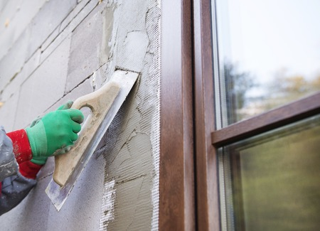 house coats: Plasterer spreading out plaster with trowel around the windows Stock Photo