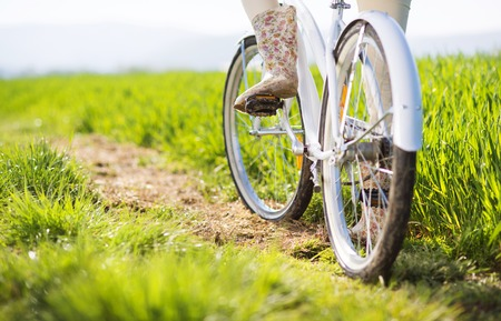 bike tire: Detail of young woman s feet in boots riding on bike in green field
