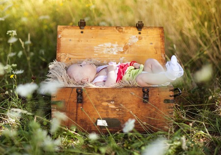 Outdoor portrait of little baby girl lying down in old wooden suitcase photo