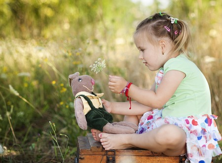 Summer outdoor portrait of cute little girl sitting on meadow with old suitcase with toys photo