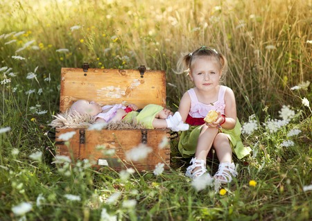 Summer outdoor portrait of cute little girl sitting on meadow with her baby sister lying in old suitcase photo