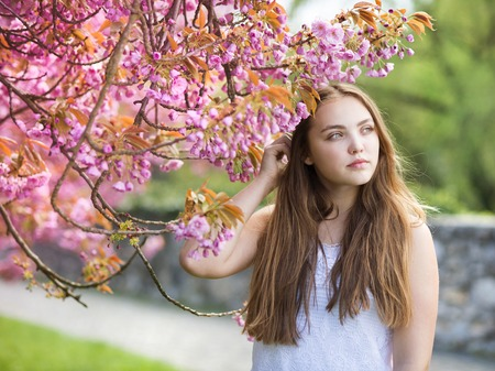 among: Beautiful girl in spring garden among the blooming trees with pink flowers Stock Photo