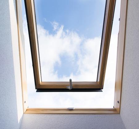 Beautiful blue sky view through roof skylight window in attic room