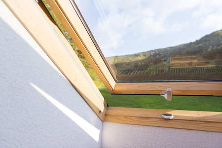 Beautiful nature view through roof skylight window in attic room  Stock Photo