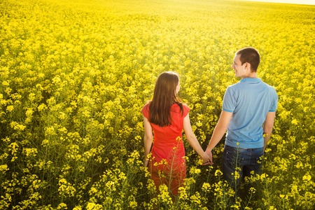 happy young couple: Happy young couple in love is walking and holding hands in yellow colza field
