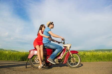 Happy young couple in love on retro motorbike driving togetger and ejoying the trip in green field photo