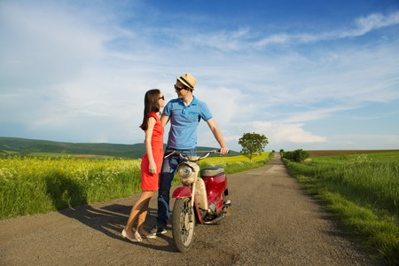 Happy young couple in love with retro motorbike is kissing on road near the field photo