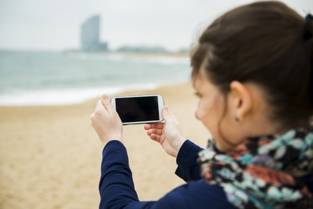 Portrait of pretty young traveler taking picture with cell phone on the beach on a cold day  photo