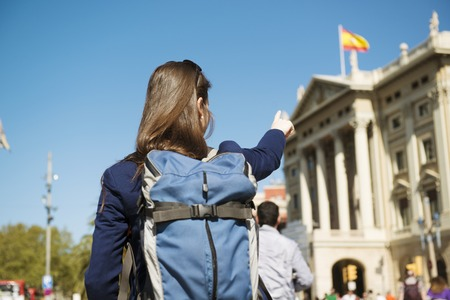 pilgrimage: Pretty young female tourist with backpack in front of the building in Barcelona city, Spain