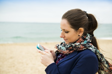 Portrait of pretty young traveler with cell phone on the beach on a cold day  photo