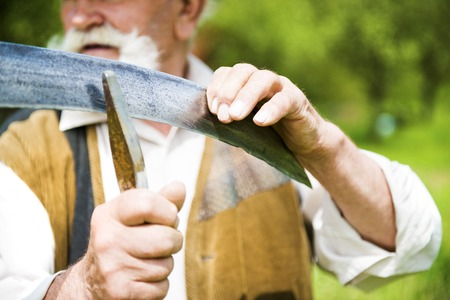 Old farmer with beard sharpening his scythe before using to mow the grass traditionally Stock Photo