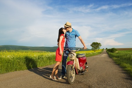 love kissing: Happy young couple in love with retro motorbike is kissing on road near the field