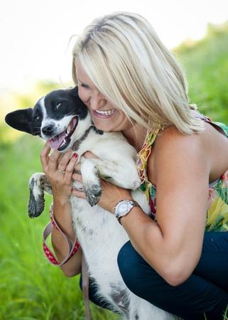 amigos abrazandose: Hermosa mujer rubia joven está abrazando y jugando con su perrito lindo al aire libre Foto de archivo