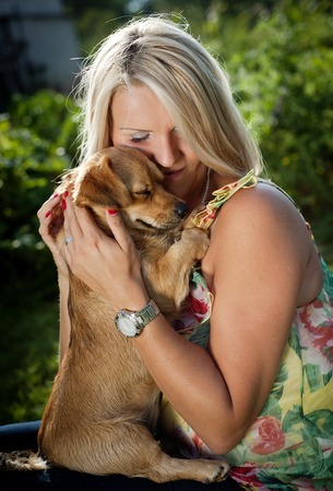 Beautiful young blonde woman is hugging and playing with her cute puppy outdoor photo
