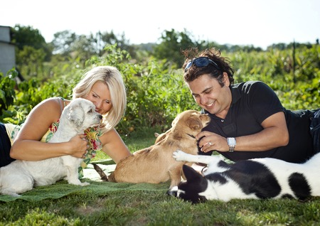 man dog: Happy young couple is laying down on grass and playing with their dogs