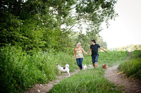 Happy young couple is walking their two dogs in green nature photo