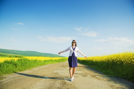 Pregnant woman on countryside road in the middle of yellow canola field photo