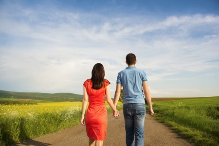 Happy young couple in love walking and holding hands on countryside road next to the colza field photo