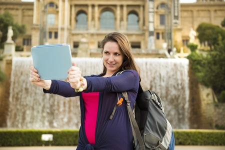 take a history: Pretty young female tourist taking selfiein front of the fountain in Barcelona, Spain  Stock Photo