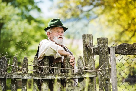 Old farmer with beard and hat standing by the lath fence with empty tins on top photo