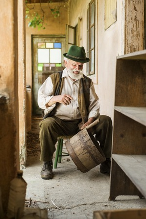 agriculturalist: Old farmer with beard and hat is working by his farmhouse