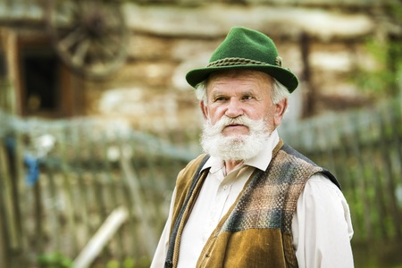 Old farmer with beard and hat standing in backyard garden by farmhouse photo
