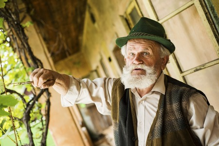 gaffer: Old farmer with beard and hat standing by his farmhouse